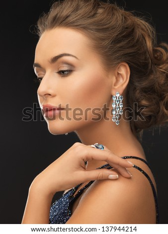 woman in evening dress wearing diamond earrings and ring - stock photo