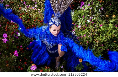 Woman in expensive exotic carnival suit pose in meadow of flowers. - stock photo