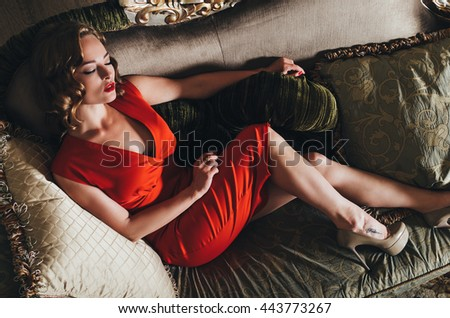 Woman in fashion red dress. Luxury indoor photo.