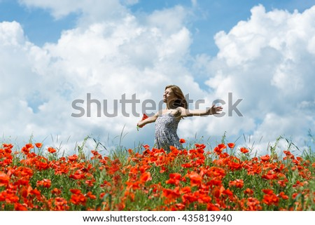 woman in field of red poppies - stock photo