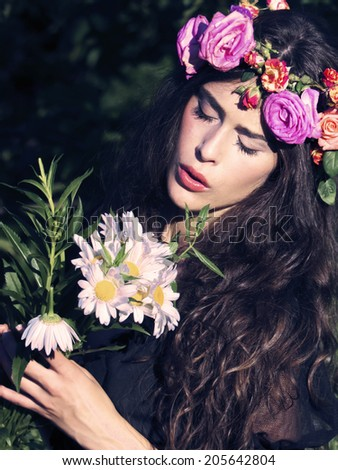 woman in field with flowers in hair - stock photo