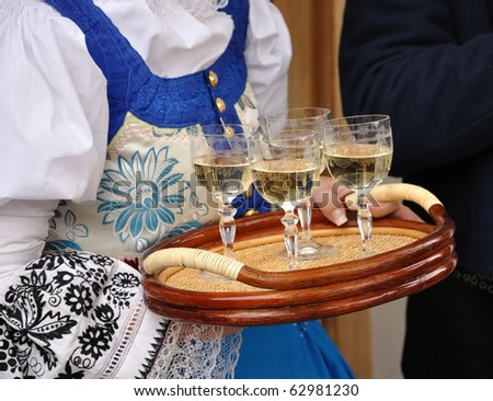 Woman in folk costume is holding plate with glass of wine - stock photo