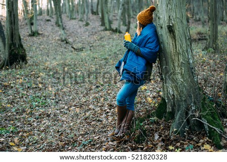 Woman in forest holding hot drink in thermos