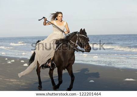 woman in formal dress galloping on horseback on beach - stock photo