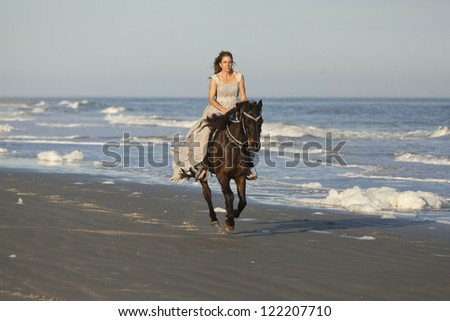 woman in formal dress riding arabian horse on the beach - stock photo