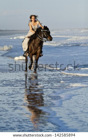 woman in formal dress riding galloping horse through surf. - stock photo