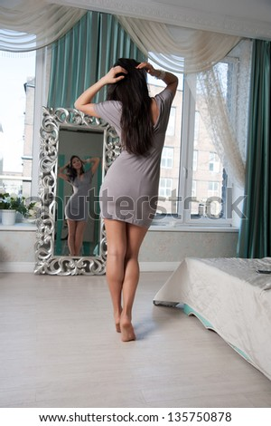 woman in front of a mirror measures a gray dress
