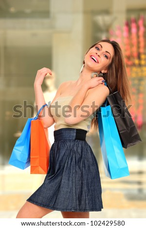 Woman in front of a shop Window with shopping bags