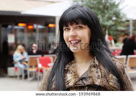 woman in front of an outdoor cafe - stock photo
