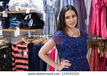 Woman in front of clothing display with hand on hip and smiling