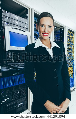 Woman in front of mainframe and communication racks in data-center for large organisation