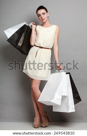 Woman in full length sale and retail time. Girl with black and white shopping bags in hands on grey background in studio. - stock photo