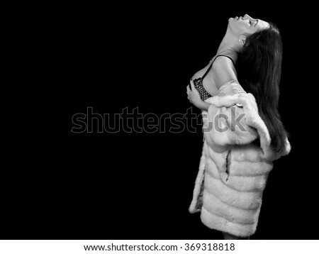 woman in fur coat on black background with copyspace, monochrome