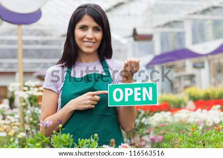 Woman in garden center pointing at the open-sign while smiling