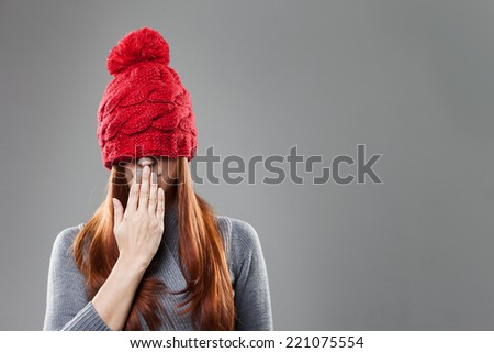 Woman in Gary Suit Covering Eyes with Red Bonnet with Hand on Lips. Isolated on Gray Background.