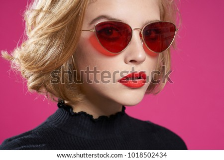 woman in glasses on a pink background