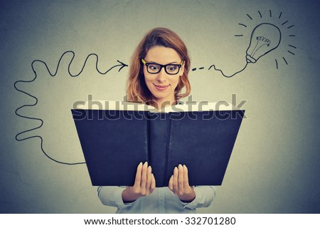 Woman in glasses reading big book comes up with an idea  - stock photo