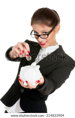 Woman in glasses saving money in a piggybank - isolated over a white background. - stock photo