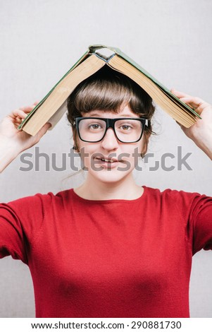 Woman in glasses with a book on his head. On a gray background.