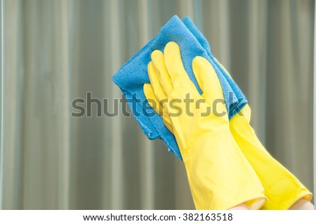 Woman in gloves cleaning mirror with rag - stock photo