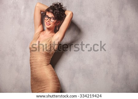 woman in golden dress holding her hair and smiling while posing at the camera