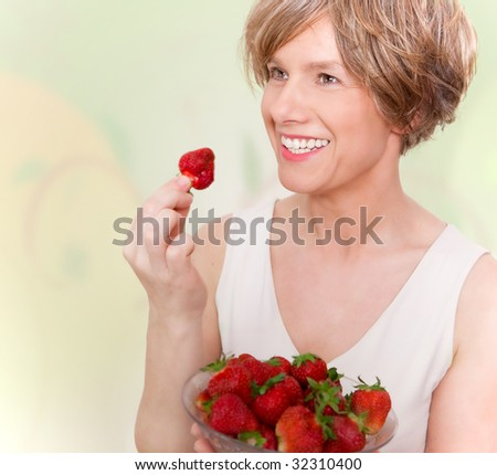 Woman in good mood eating strawberries. Healthy lifestyle. - stock photo