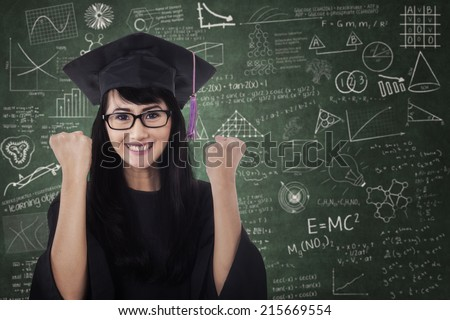 Woman in graduation gown expressing success in the class - stock photo