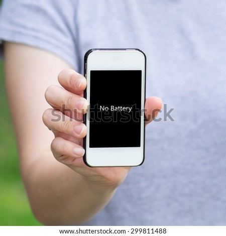 "Woman in gray shirt show mobile phone with message ""No Battery"" on the screen"
