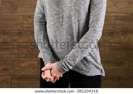 woman in gray sweater holding hands together