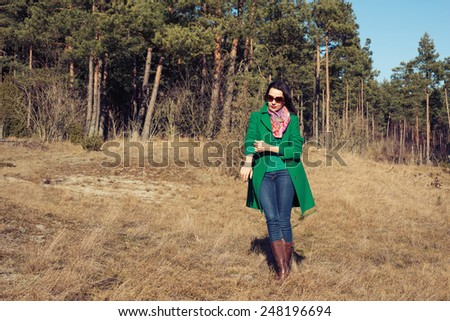 Woman in green coat walks on nature spring