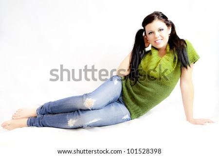 Woman in Green Sweater and Jeans in the Studio - stock photo