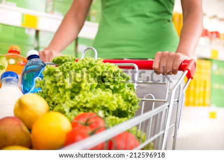 Woman in green t-shirt pushing a shopping cart at store with shelves on background. - stock photo