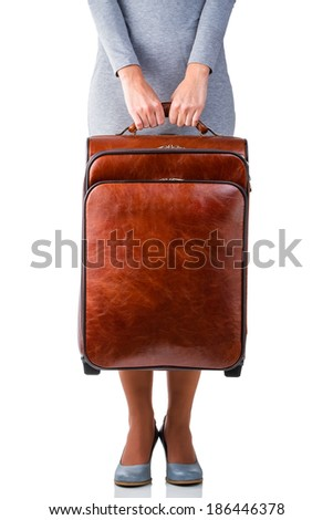 Woman in grey dress holds leather suitcase with copy space - stock photo