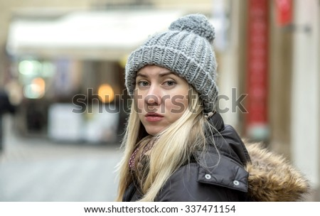 Woman in grey winter hat in the city