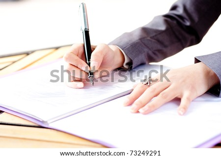 woman in grey write by pen on paper. Businesswoman signs. Isolated on white background