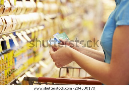 Woman In Grocery Aisle Of Supermarket With Coupons - stock photo