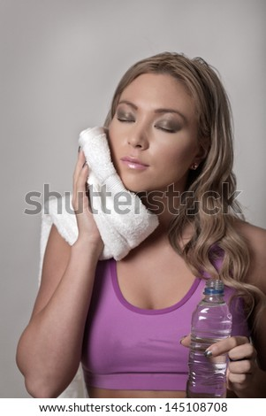 Woman in gym clothes with a towel over her shoulder drinking bottled water