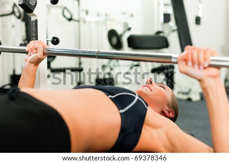 Woman in gym exercising for better fitness with a barbell - stock photo