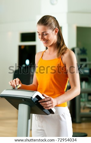 Woman in gym or health club reading her training plan which is stored on a modern key system - stock photo