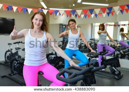 Woman in gym thumbs up after fitness training - stock photo