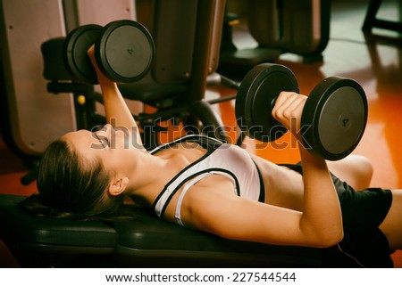 Woman in gym training with dumb bells - stock photo