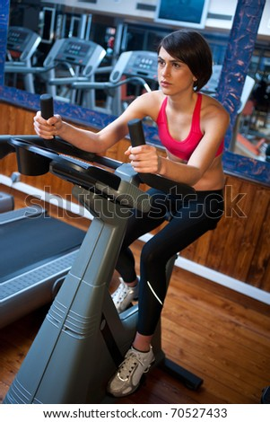 woman in gym working on bicycle machine