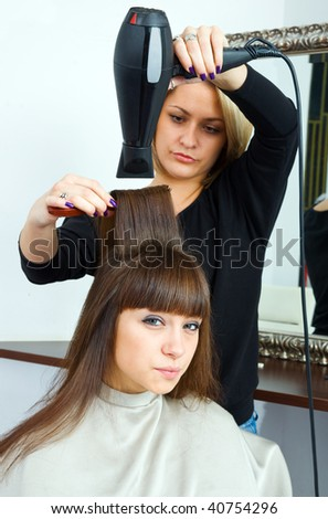 woman in hair salon having treatment with hair blower