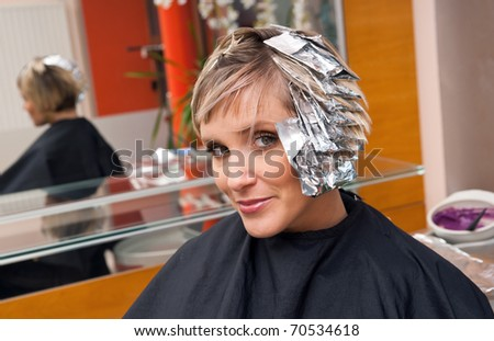 woman in hair salon with coloring foil on her head - stock photo