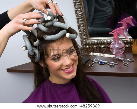 woman in hair salon with curlers on her hair - stock photo