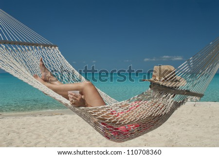 woman in hammock at Hawks Nest resort in Cat Island Bahamas - stock photo