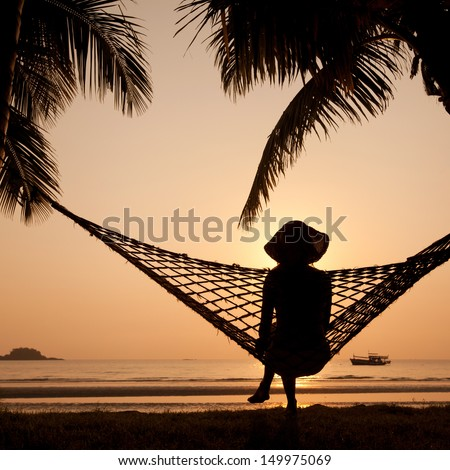 woman in hammock enjoying sunset on the beach