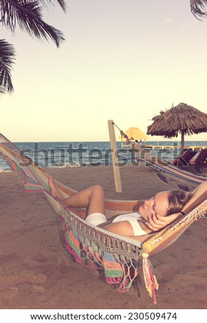 Woman in hammock on beach, vintage color - stock photo