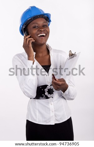 Woman in hard-hat having conversation on her cell phone. - stock photo