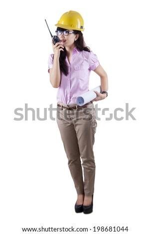 Woman in hard hat using radio communication while holding a blueprint. Isolated on white background - stock photo